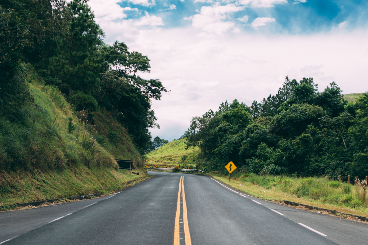 A winding 2-lane blacktop with double yellow lines snakes through the countryside.