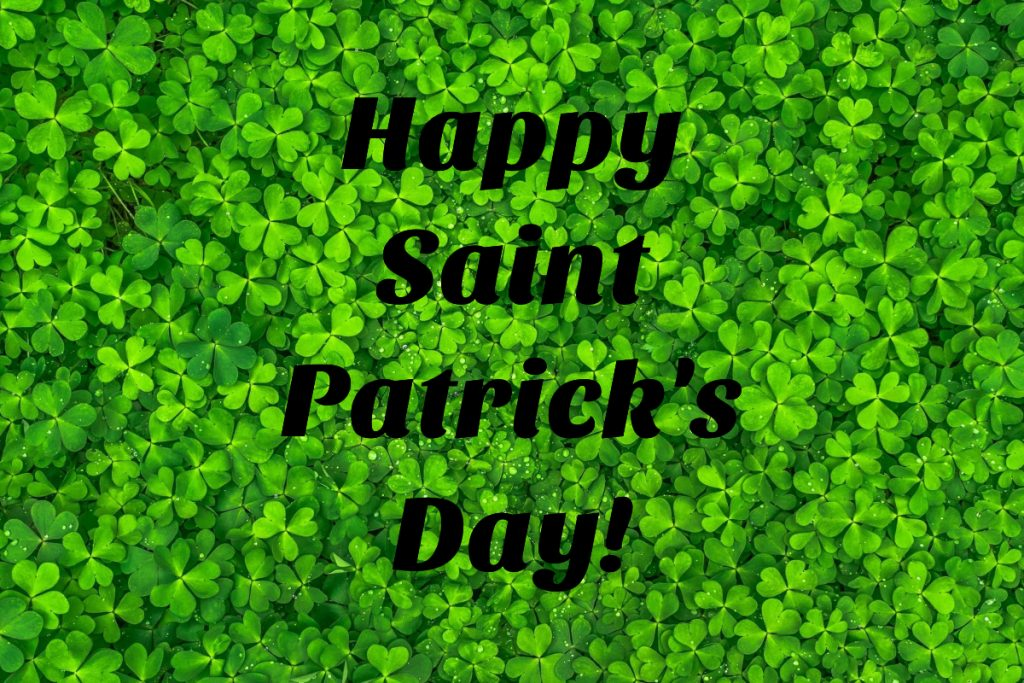 Happy Saint Patrick's Day! written on a bed of bright green 3 leaf clover.