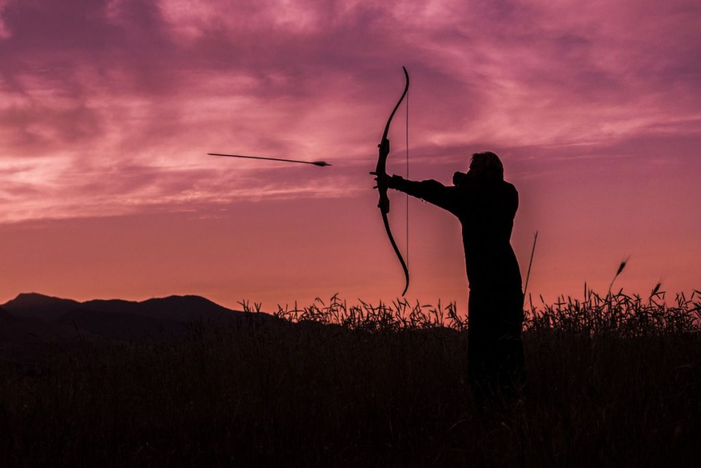 A female archer releases an arrow from a recurve bow . She's standing in a field with a dusky purple sky in the background.