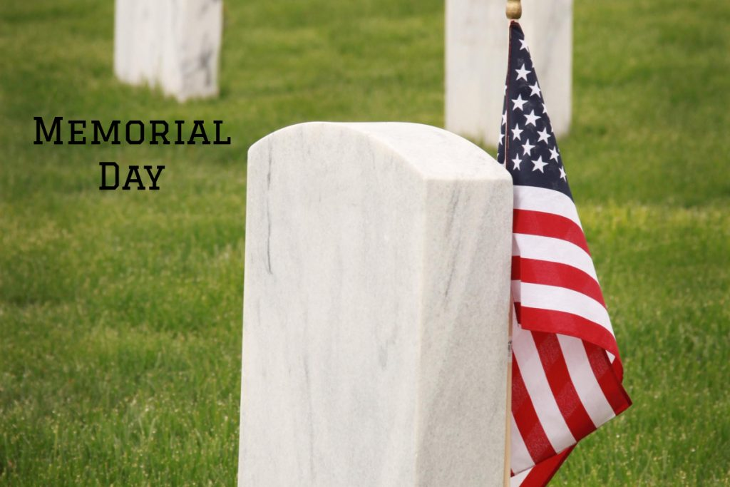 Memorial Day scene. Marble headstones with an American flag.
