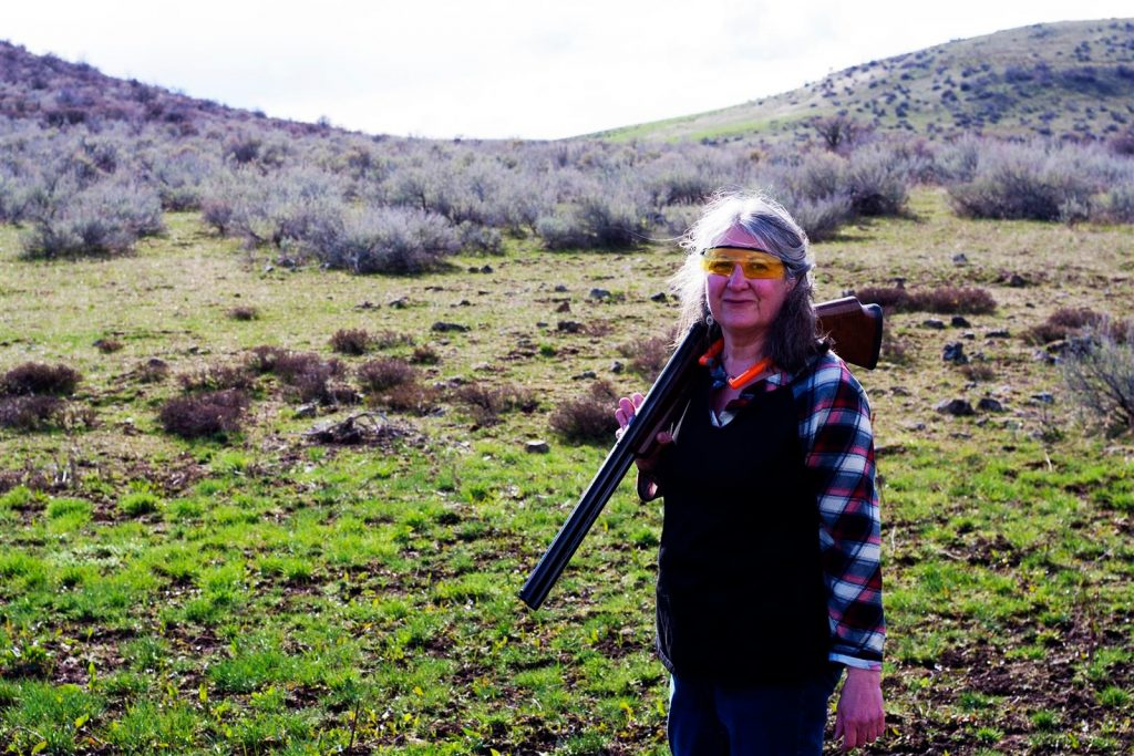Photo of Linda Bittle, with shotgun over shoulder, standing in Idaho field.